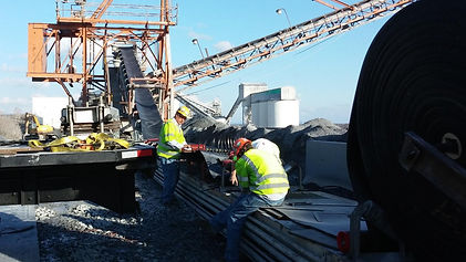Three members of the installation and vulcanizing crews for conveyor belt installation on-site services from Virginia Carolina belting, showing a finger-splice being lifted and installed at a customer's aggregate site.