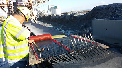 One experienced crew member examining a finger splice job on a conveyor belt installation on-site, mounds of aggregate and rocks in the background with extended conveyor belt system visable.