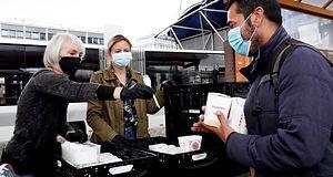 Das Foto zeigt Mitarbeiter der Hilfsorganisation Care4Cologne e.V. bei der Essensausgabe am Kölner Hauptbahnhof.