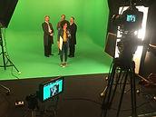 Das Foto zeigt die Reporterin Siham in einer Grünstanze neben Darstellern für die Dreharbeiten zur Maus-Sachgeschichte über die Geschichte des Reichstages in Berlin.
