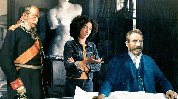 Das Foto zeigt eine Bildmontage, in der Reporterin Siham für die Sendung mit der Maus zwischen dem Architeken des Reichstages und Kaiser Wilhelm steht.