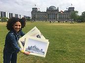 Das Foto zeigt Siham mit historischen Bildern vor dem Reichstag in Berlin.
