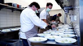 """Das Foto zeigt Mitarbeiter des Unternehmens """"DEINspeisesalon"""" bei der Zubereitung von Essen in der Küche."""