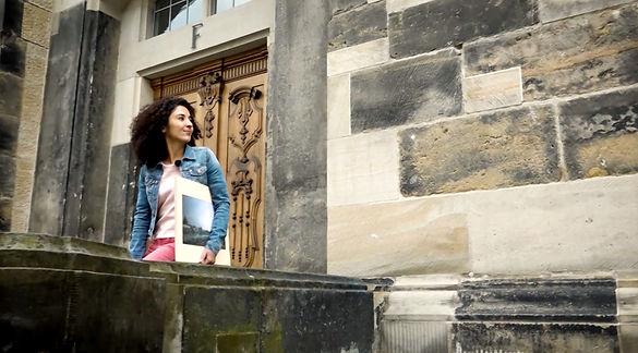 Das Foto zeigt Maus-Reporterin Siham vor den hellen und dunklen Steinen der Frauenkirche in Dresden.