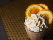 Boozy milkshake cocktail from neighborhood bar The Sixth in Chicago Lincoln Square and Ravenswood neighborhood. Orange fluffy cool drink