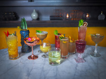 Cute colorful instagrammable cocktails from The Sixth bar in Chicago Lincoln Square nighborhood. Tiki unique glassware. Bright yellow cute bar seatng