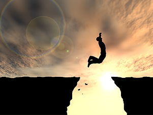 Concept or conceptual young man or businessman silhouette jump happy from cliff over  gap sunset or