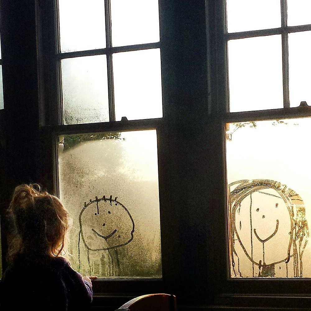A girl draws on window condensation in a smartphone photograph by Dunedin photographer Edith Leigh