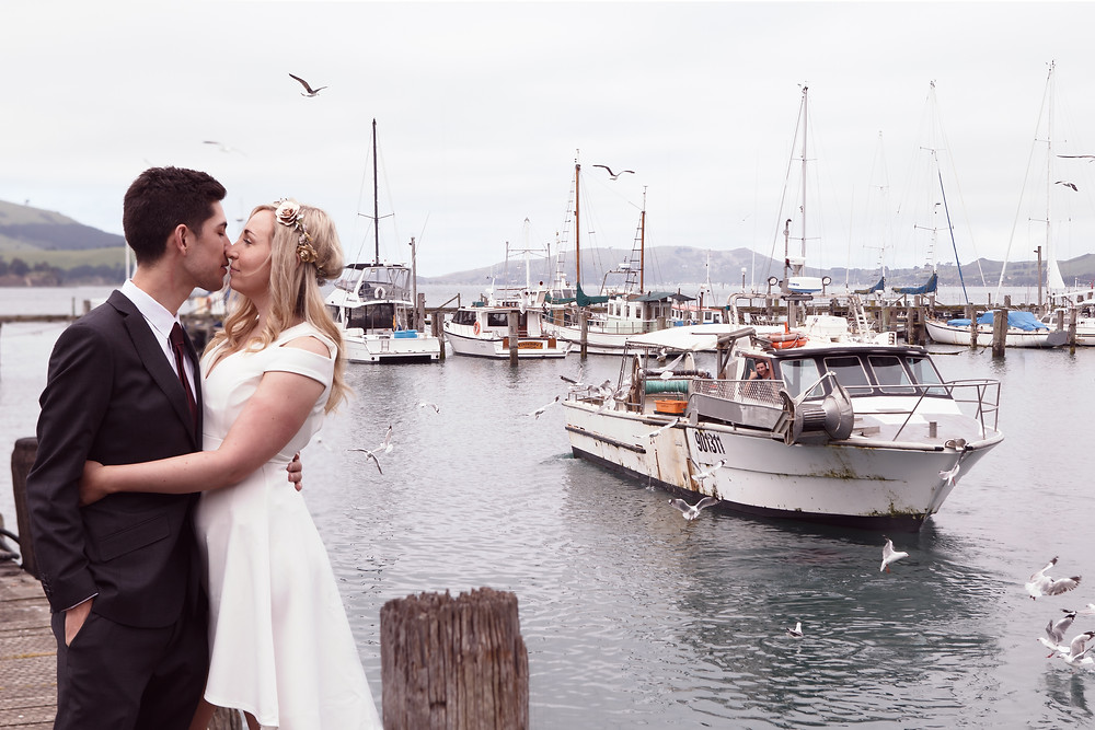 Bride and groom kiss at Careys Bay, Dunedin, while a fisherman cheers them on from his boat