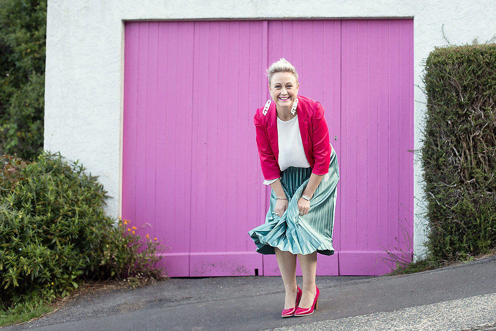 A woman smiling in front of a pink garage during a personal branding photoshoot