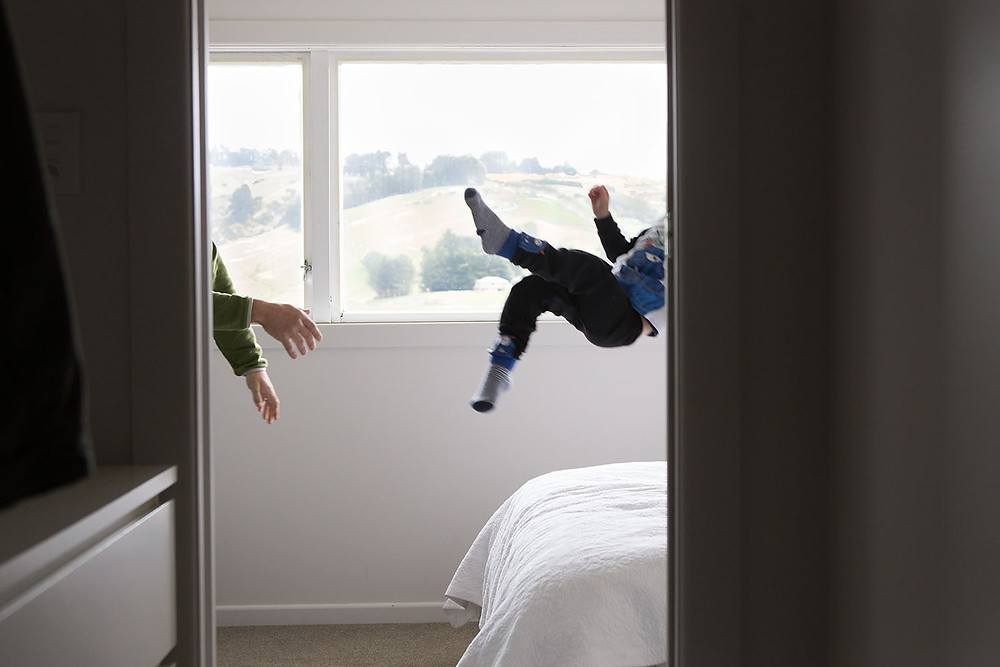 Documentary style family photography that shows a child being thrown on the bed in play