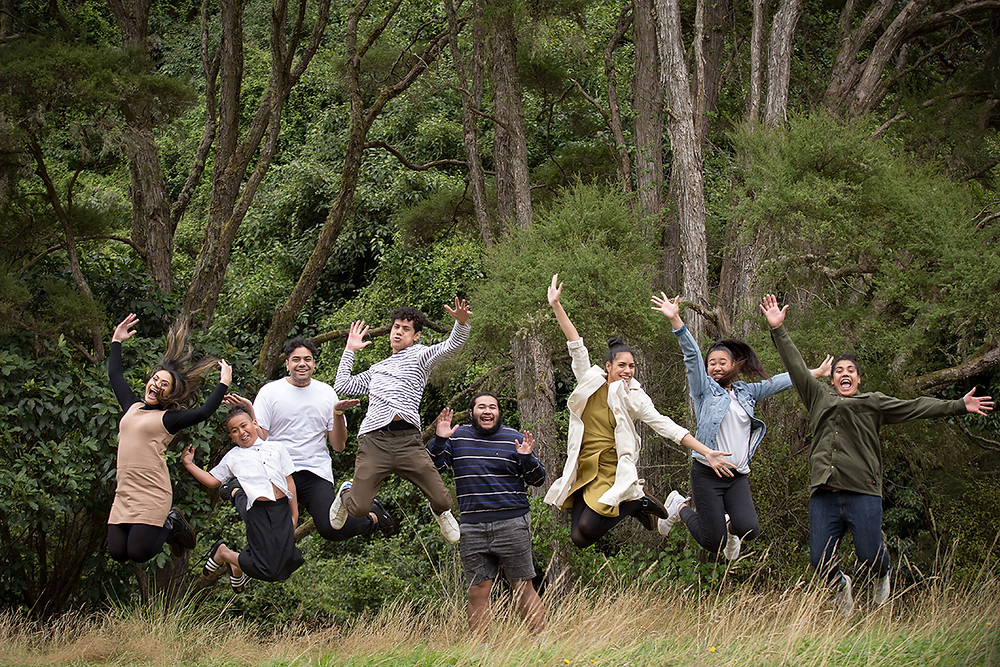 Extended family siblings jump together for a fun picture during their family photoshoot
