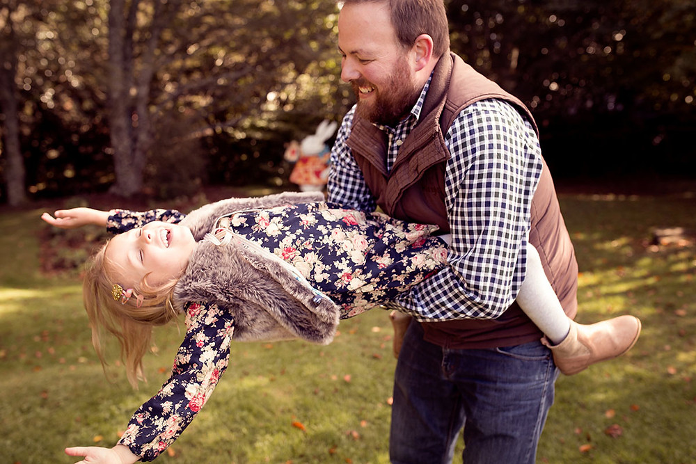 Dad throwing daughter up in the air during a family photoshoot with Dunedin photographer Edith Leigh