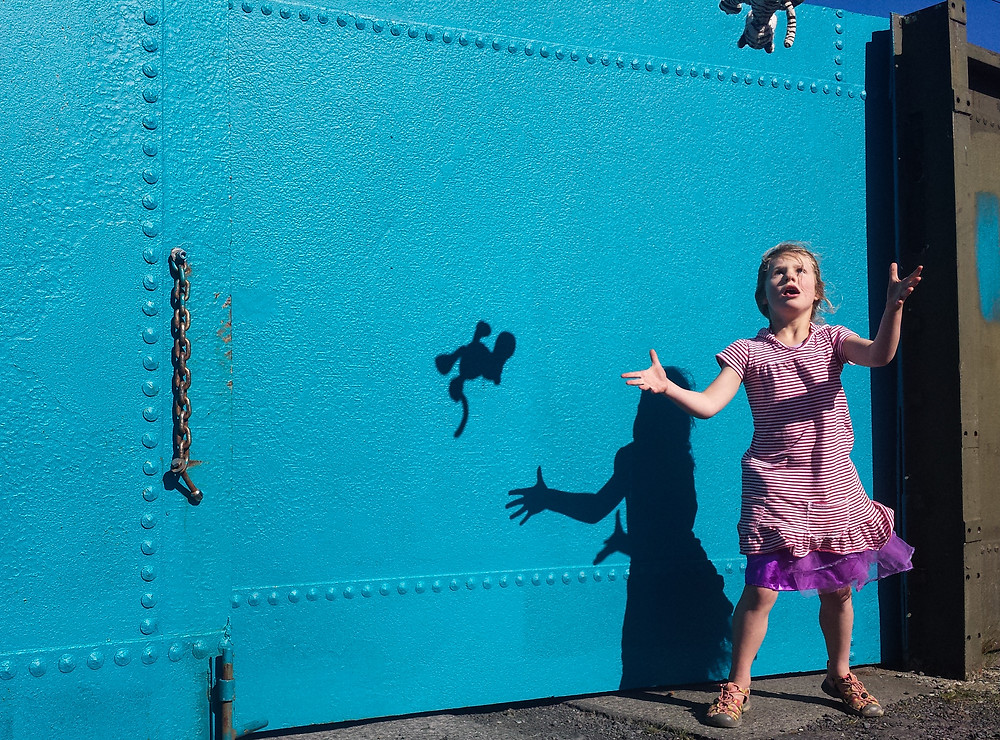 Dunedin photographer Edith Leigh captures a girl and her shadow plays with her toy in front of a blue door