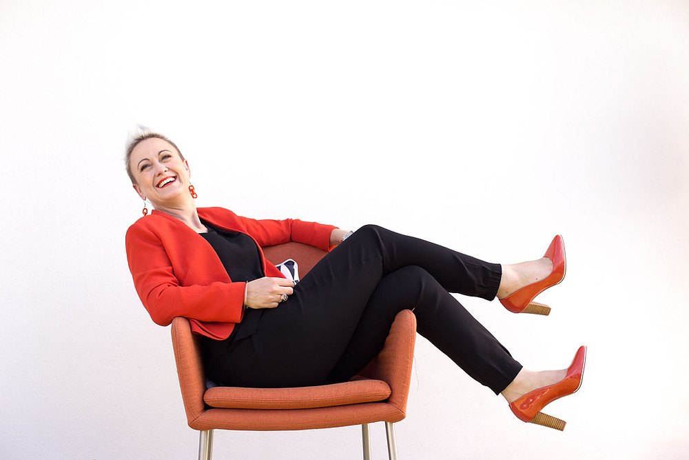A woman naturally and casually posed in a chair laughing for the camera during a headshot and personal branding photoshoot.
