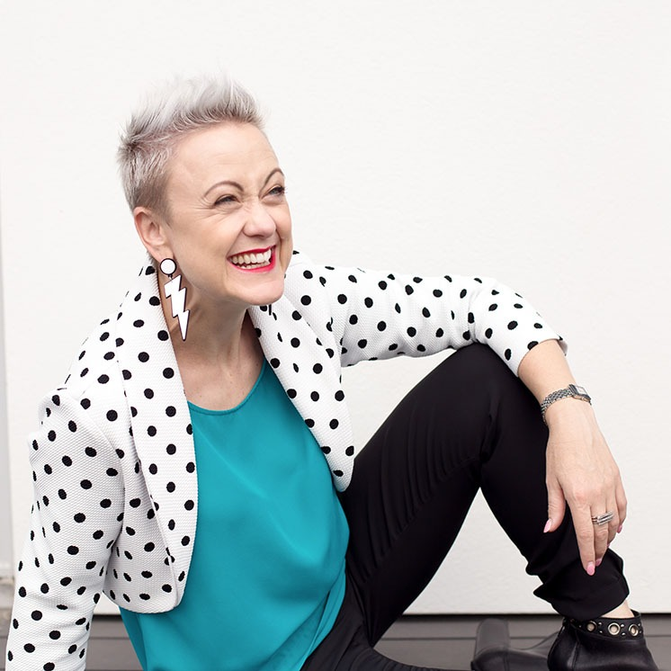 Woman in a jacket with dots laughing for the camera in a relaxed pose