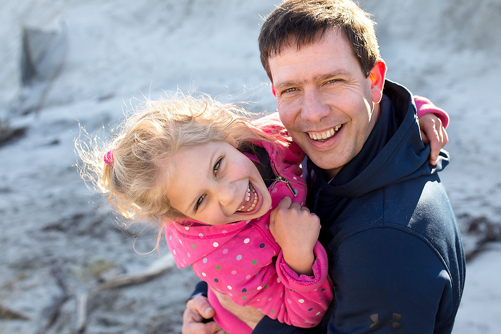 A girl and her dad laughing together for a natural family picture on a Dunedin beach