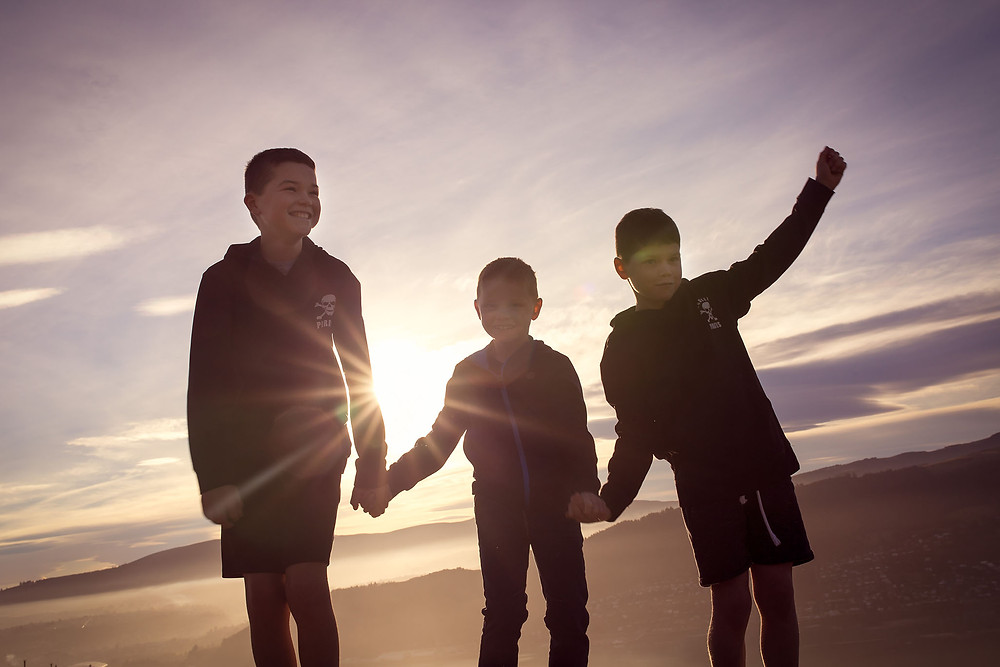 Three brothers play together as the sun sets on a hillside above Otago Harbour in Dunedin