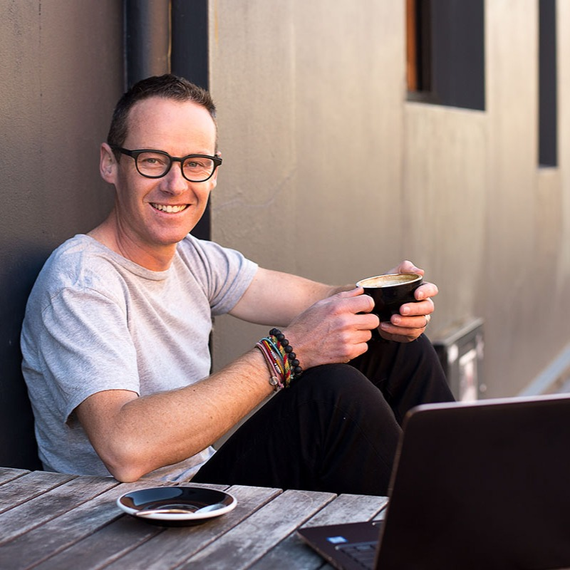 Dunedin business owner sits outdoors at a cafe with a coffee and his laptop