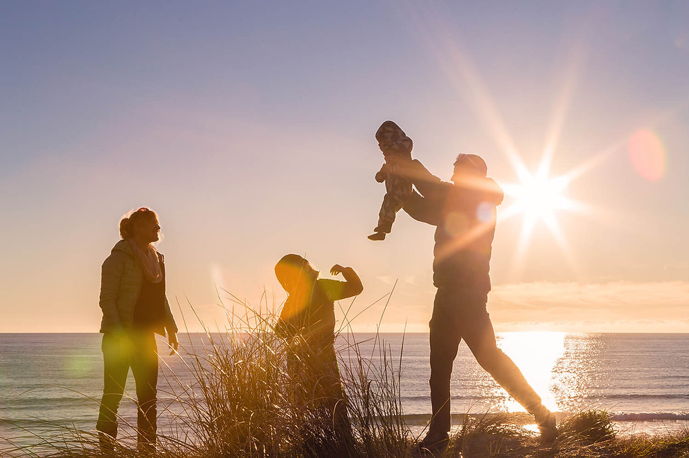 A family enjoying time at the beach in Dunedin during a lifestyle family photography session