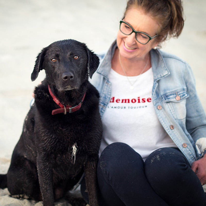 Picture of a woman and a black dog sitting together on the beach