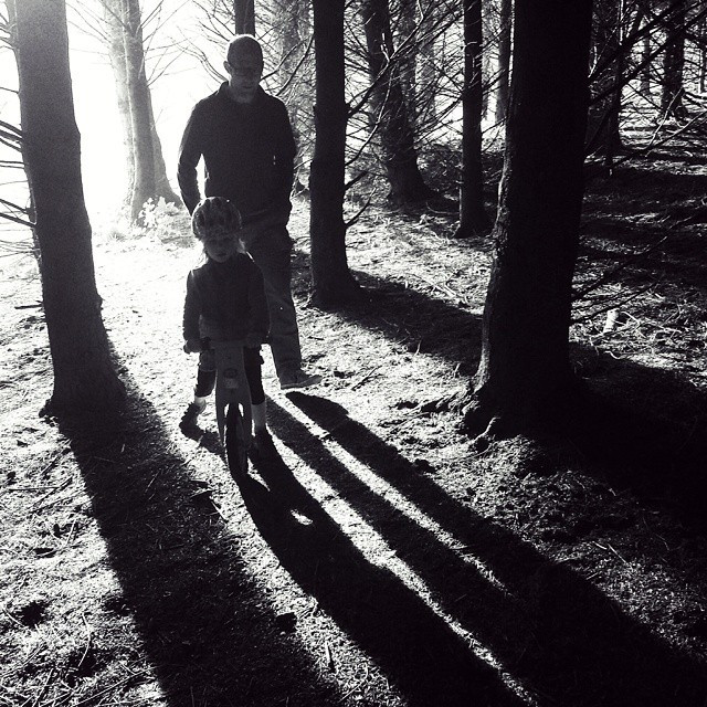 A man and a girl on a balance bike create long, striking shadows in a forest as captured on a smartphone by Dunedin photographer Edith Leigh