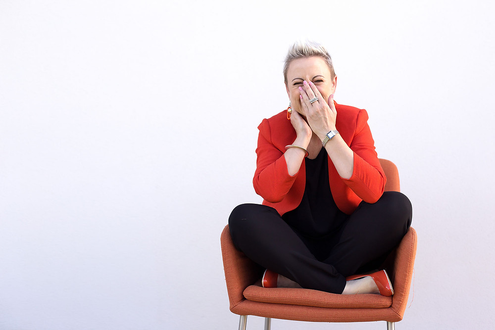 Woman sitting on an orange chair for a headshot session