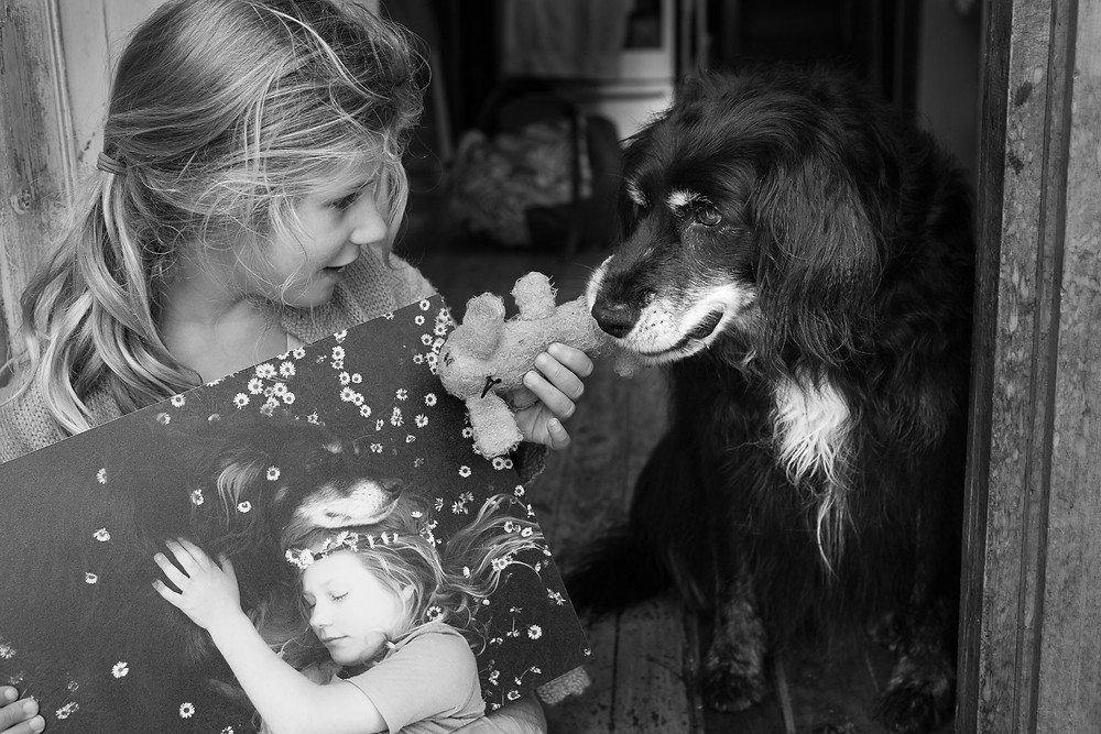A girl plays with her dog while holding a stunning black and white print of them both to hang in her bedroom