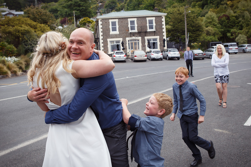 Brother and nephews embrace bride during a wedding at Careys Bay