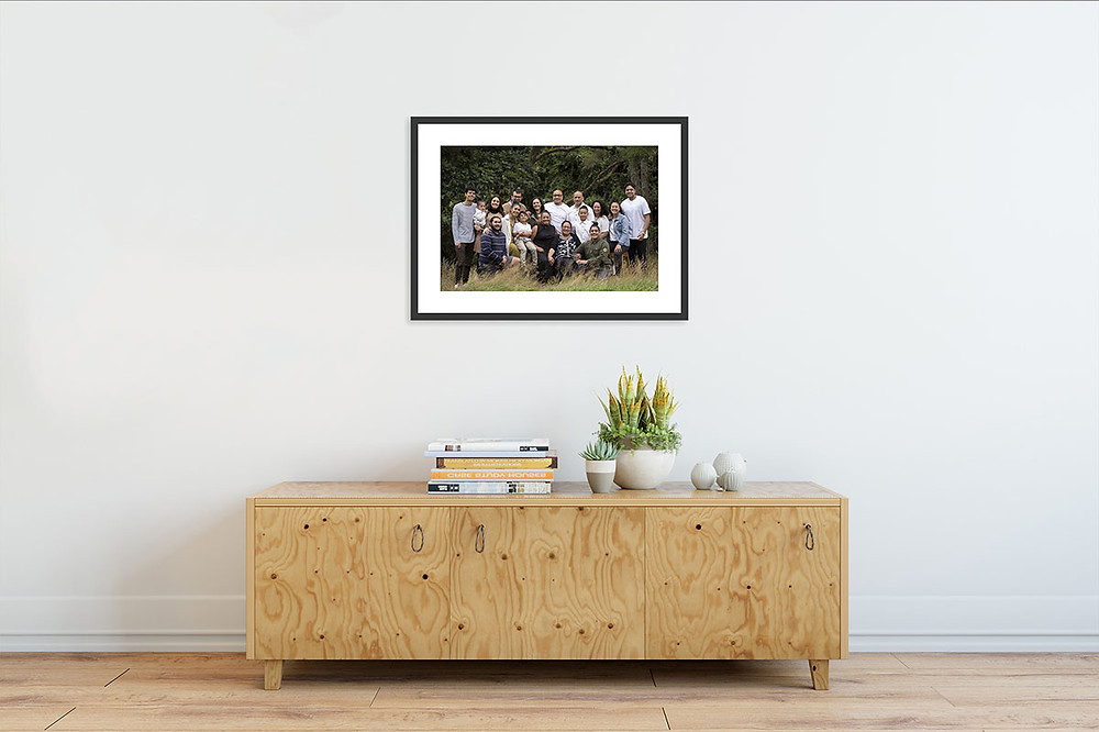 Printed and framed picture of an extended family group hung on the wall