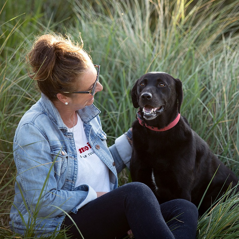 A woman and a black dog in long grass sit for a photograph