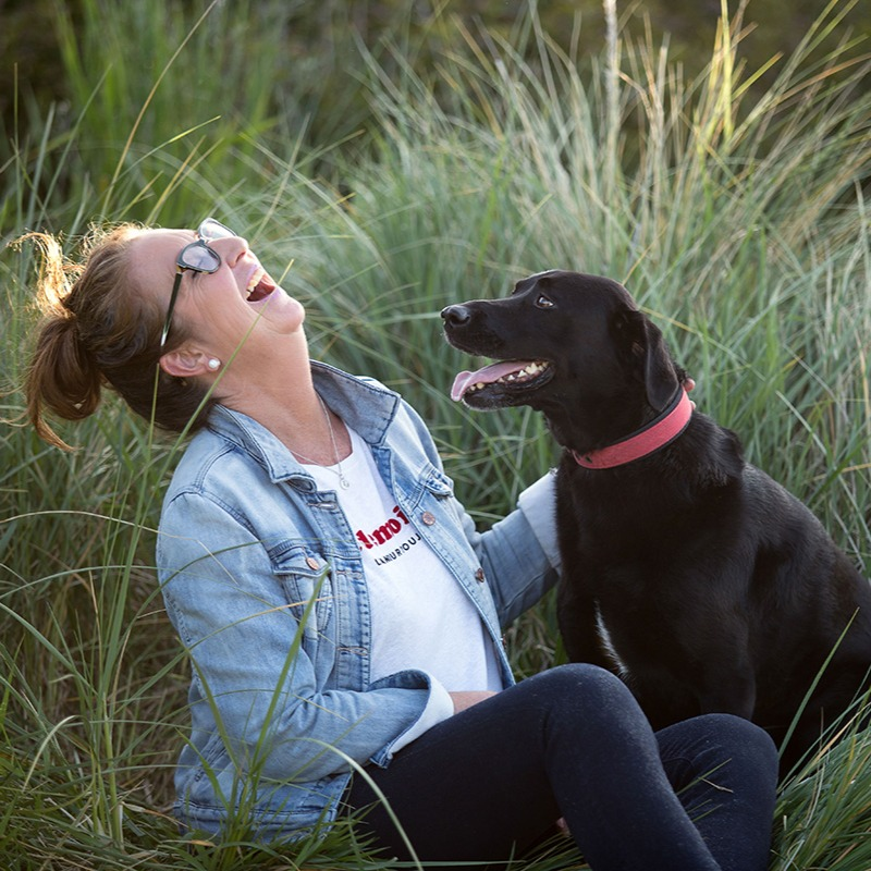 Woman laughing with her dog in long grass near the beach