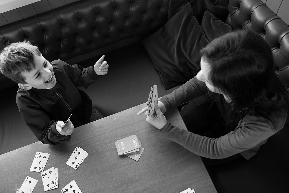 Mum and son play a card game at a Dunedin cafe during a family photoshoot