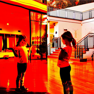 Girl studies her reflection in a coloured panel at an art gallery - mobile phone photograph by Dunedin photographer Edith Leigh