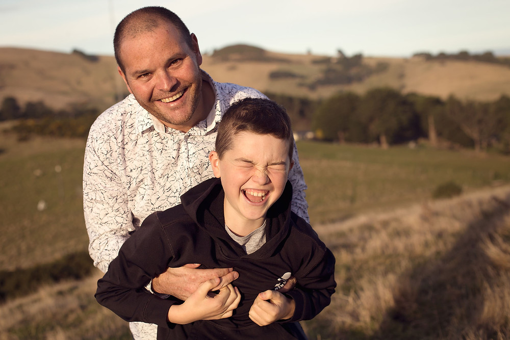 Father and son play during a family photoshoot in Dunedin