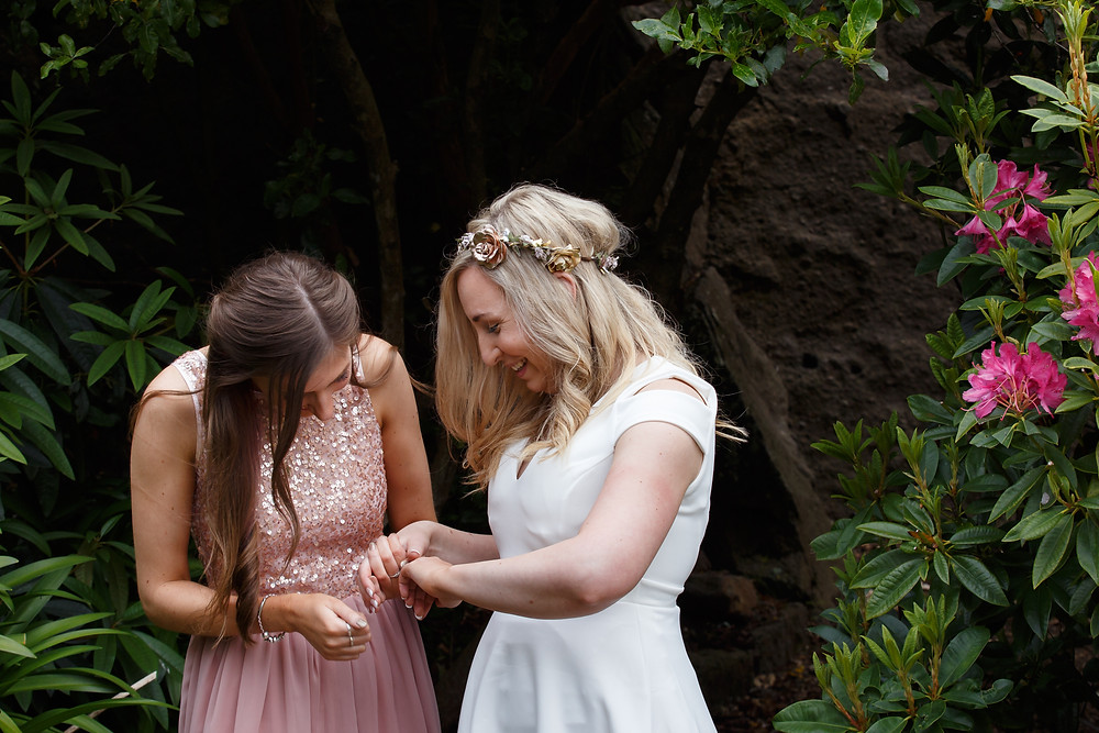 The bride's best friend admires her new wedding ring during her garden wedding in Dunedin
