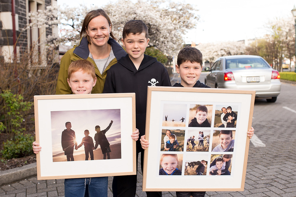 A Dunedin family with framed Fine Art family prints ready to hang on the wall