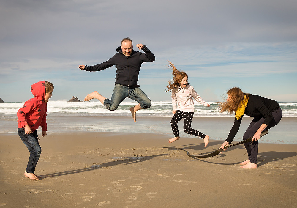 Action family portrait of a family playing on the beach in Dunedin, New Zealand
