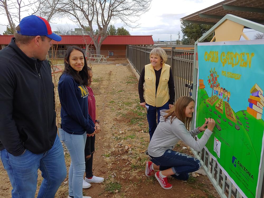 Student Volunteers sign Oasis Banner