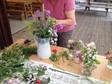 A workshop attendee working on her cut flower vessel arrangement