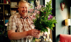 A happy workshop attendee making a hand tied bouquet.