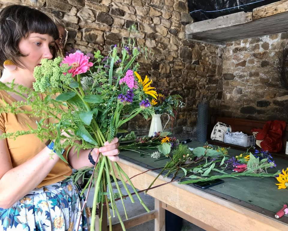 A workshop attendee making a hand tied bouquet