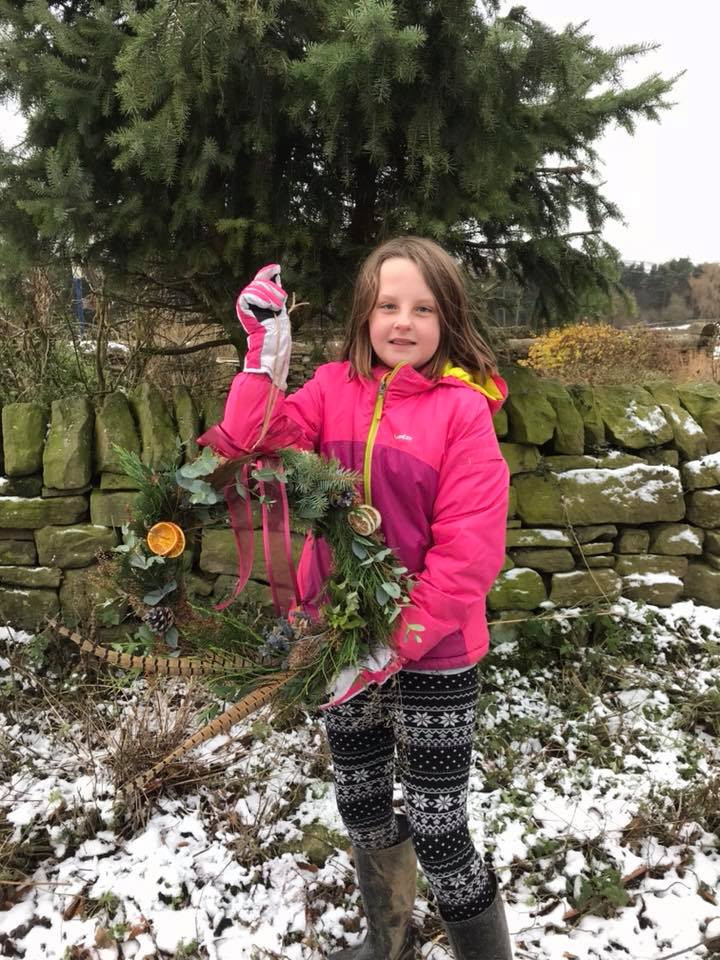 A young attendee with her christmas wreath
