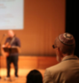A worshipper wearing a yarmulke or kippah with a Star of David on it looks toward the service leader who is playing a guitar on stage. This is what davening or prayer or worship or tefillah looks like at Beth Messiah.
