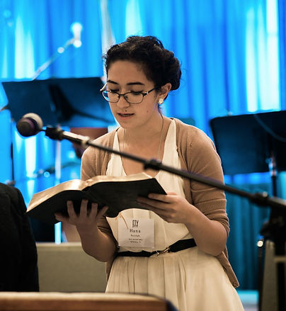 A young woman wearing glasses, a cream-colored dress, and a dusky cardigan, stands against an out of focus, spot-lit blue background, reading a translation of the haftarah. In the foreground, a microphone stand is perched in front of her.
