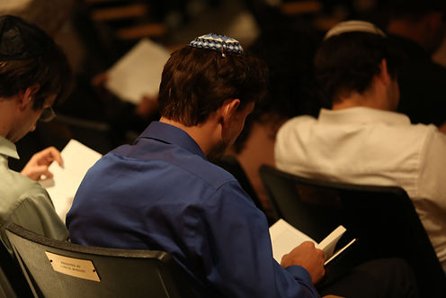 Several young men wearing yarmukes study Hebrew prayer books