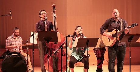 Beth Messiah's worship ensemble. From left to right: a percussionist seated behind a large bass drum strikes a cymbal; the next musician stands next to a large upright bass, eyes closed as he sings into the microphone; another seated percussionist holds a shaker in the air and sings into her microphone, a large djembe at her side; a guitarist stands and sings into his microphone, eyes closed. Three of the four have music stands in front of them.