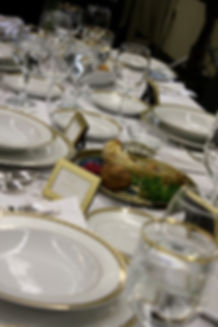 A Passover seder table set with beautiful china and glasses. In the center, a seder plate holds the traditional maror (horseradish), parsley, egg, charoset, and shankbone.