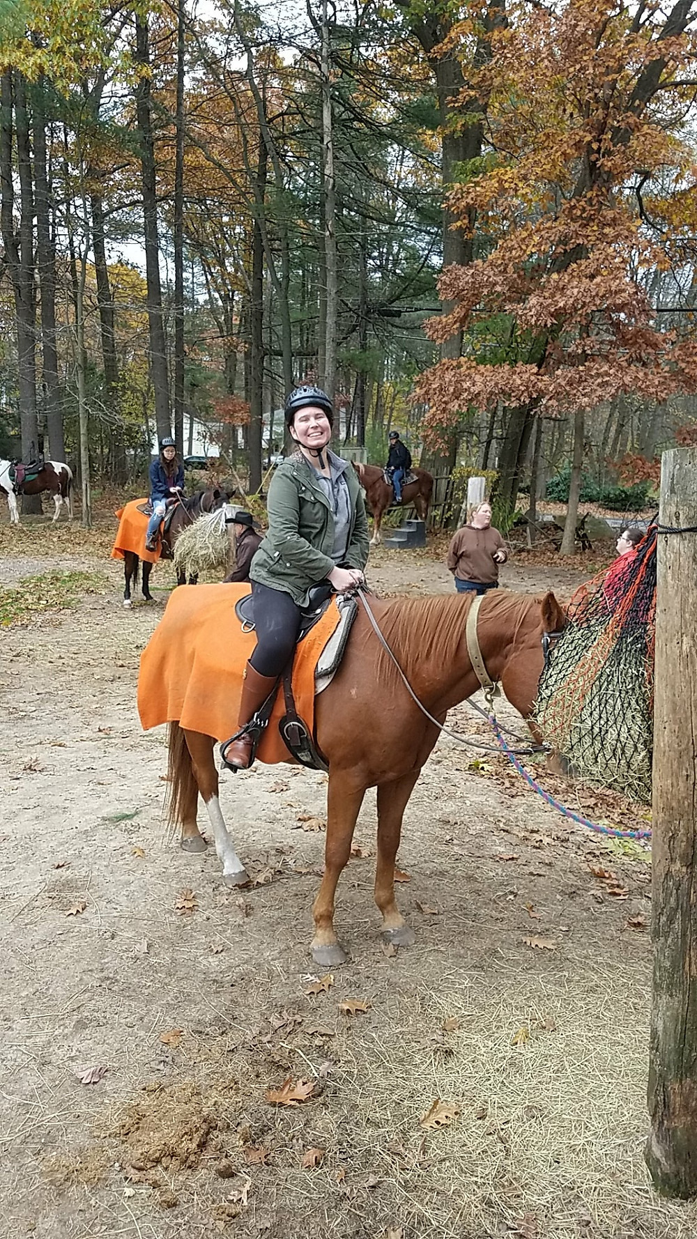 smiling woman riding a horse