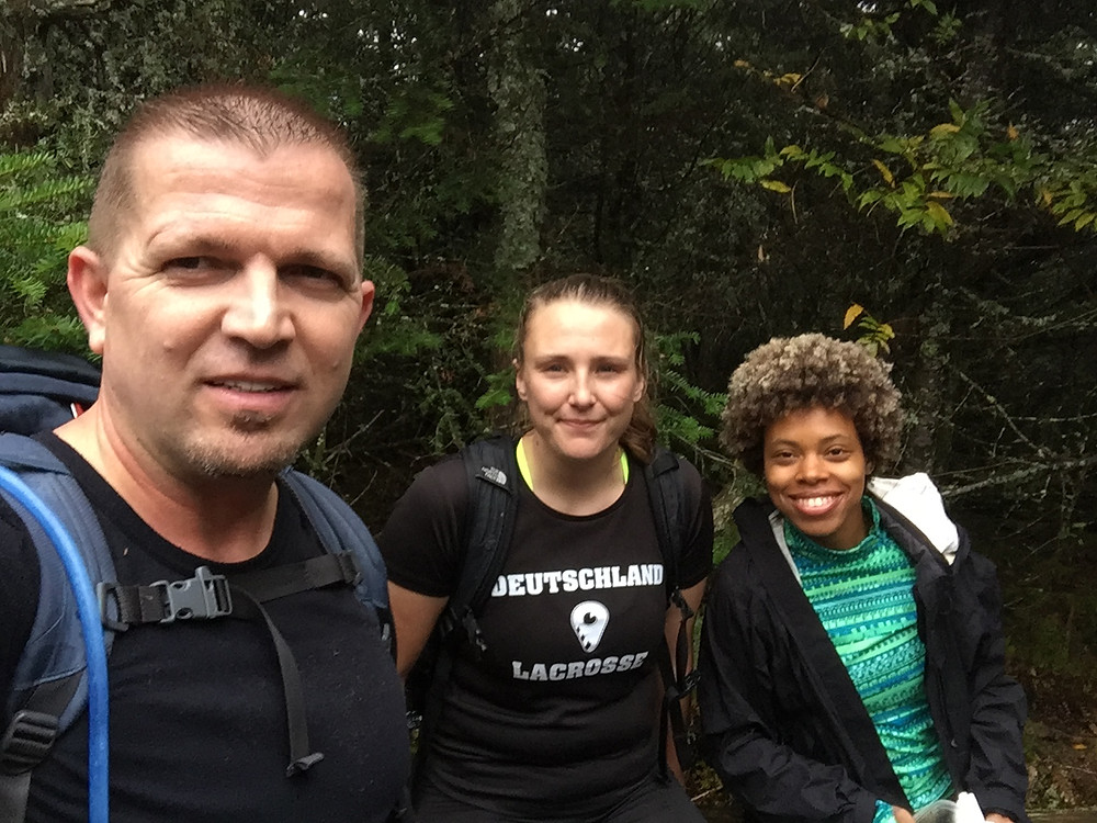 Three people looking into the camera while hiking with green leaves in the background